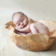 Newborn in big wooden bowl