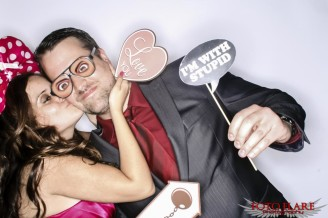 Photo booth image of a couple kissing with silly props
