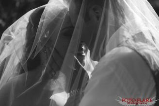 B&W photo of the bride and groom kissing under veil